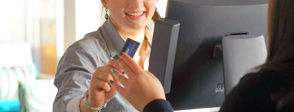 hymyilevä asiakaspalvelija ojentaa maksukortin takaisin asiakkaalle